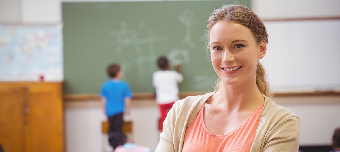 Teacher smiling in the foreground, two boys at a chalkboard in the background