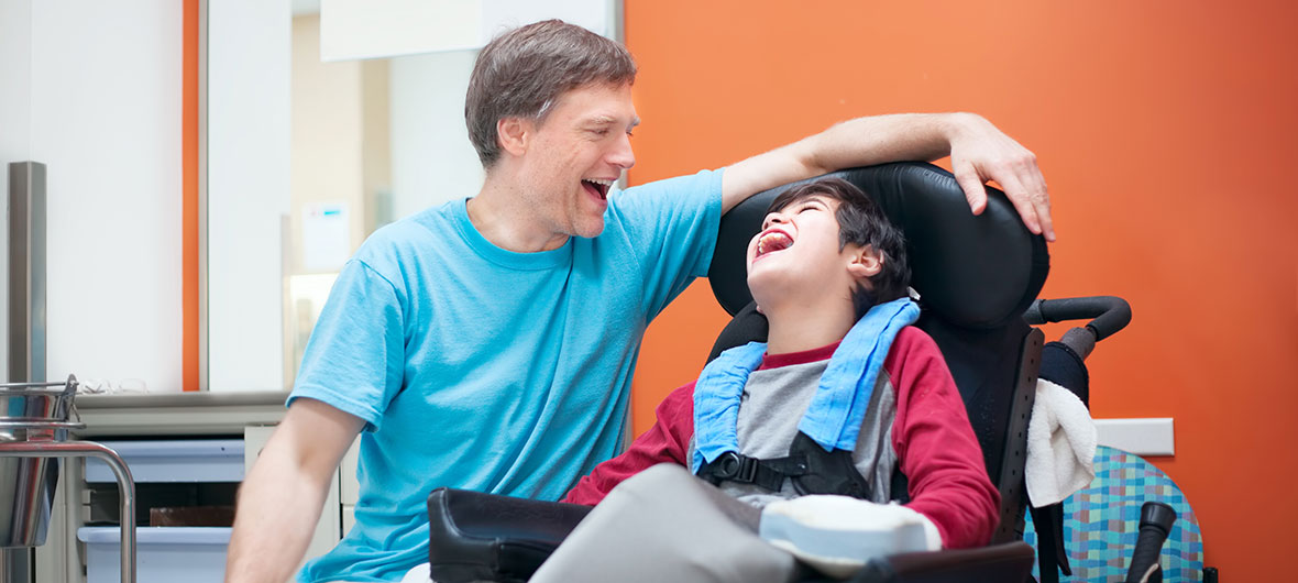 A man beside a boy in a wheelchair laughing together